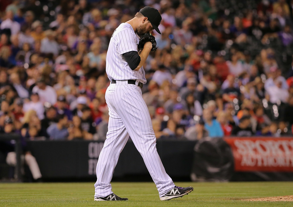 . DENVER, CO - AUGUST 15:  Adam Ottavino #0 of the Colorado Rockies returns to the mound as he works against the Cincinnati Reds at Coors Field on August 15, 2014 in Denver, Colorado. Ottavino collected the loss as the Red defeated the Rockies 3-2.  (Photo by Doug Pensinger/Getty Images)