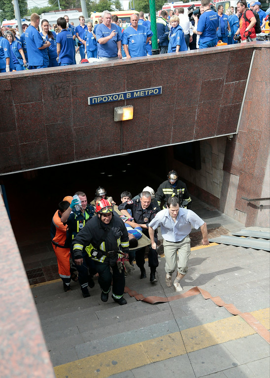 . Paramedics, a police officer and a voluenteer carry an injured man out from a subway station after a rush-hour subway train derailment in Moscow, Russia, on Tuesday, July 15, 2014.  (AP Photo/Ivan Sekretarev)