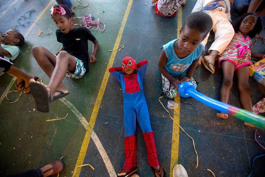 . Children pass the time at a pre-carnival celebration in Rio de Janeiro, Brazil, Friday, Feb. 1, 2013. A Police Pacification Unit, UPP, organized the party for about 80 children from surrounding shantytowns.  The UPP program aims to reduce crime, bring services to shantytown residents and increase safety in preparation for the World Cup in 2014 and the 2016 Olympic games.  (AP Photo/Silvia Izquierdo)