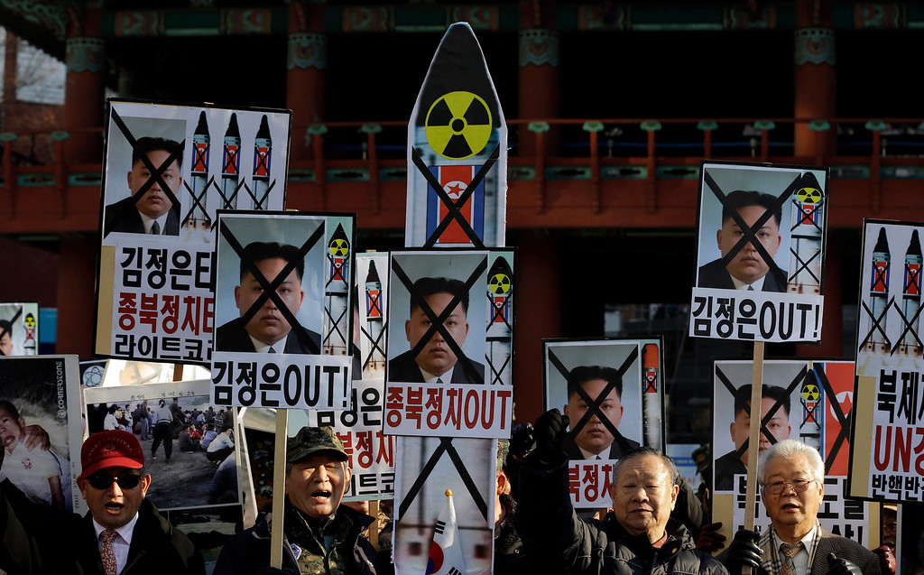 """. South Korean protesters shout slogans during a rally denouncing North Korea\'s rocket launch in Seoul, South Korea, Wednesday, Dec. 12, 2012. North Korea successfully fired a long-range rocket on Wednesday, defying international warnings as the regime of Kim Jong Un took a giant step forward in its quest to develop the technology to deliver a nuclear warhead. The letters on the sign read \"""" Out, Kim Jong Un.\"""" (AP Photo/Lee Jin-man)"""