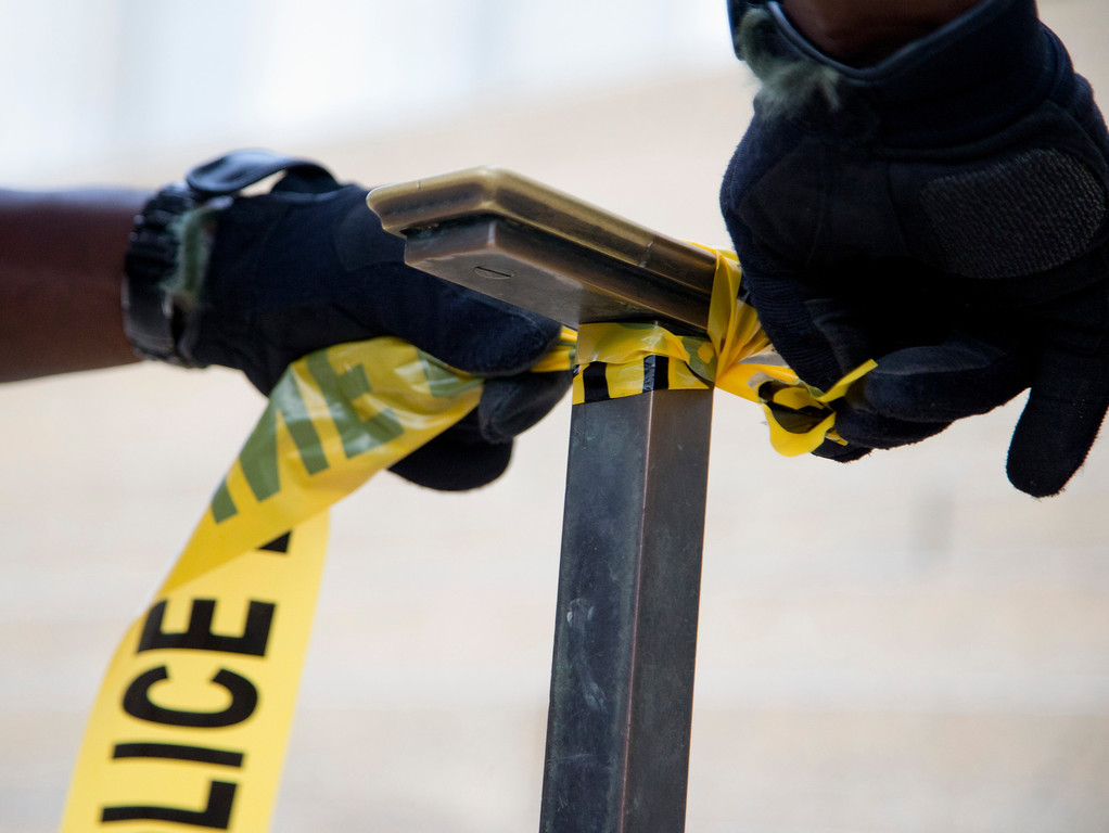 . A US Park Police officer ties police tape to a hand rail closing access to the Lincoln Memorial in Washington, Tuesday, Oct. 1, 2013. (AP Photo/Carolyn Kaster)