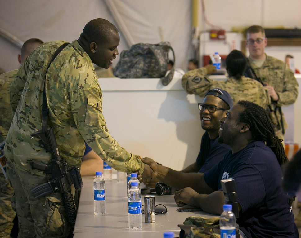 . Tampa Bay Bucanneers guard Davin Joseph (r) and Denver Broncos linebacker Von Miller (2nd r) greet a service member stationed in the Middle East during a USO/NFL tour stop March 18, 2013. This is the first USO tour for Joseph and Miller.  USO Photo by Fred Greaves