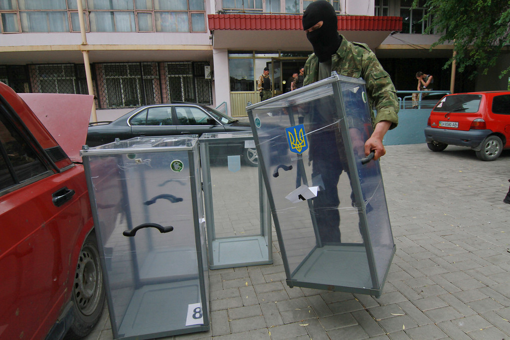 . A Pro-Russian activist carries a ballot box away from a polling station preparing to smash it, in Donetsk, Ukraine, Friday, May 23, 2014. Ukraine\'s acting government has admitted that authorities will not be able to organize the voting in parts of eastern Ukraine, overrun by pro-Russian insurgents. (AP Photo/Photomig)