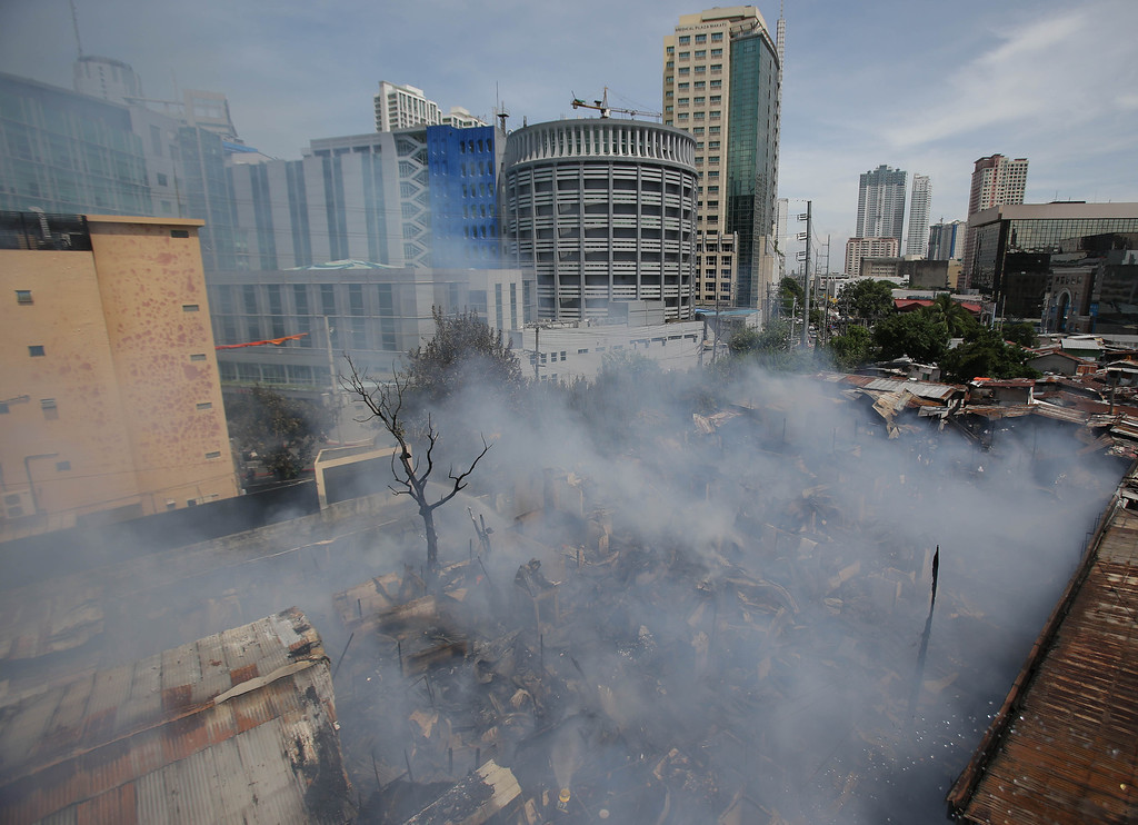 . Smoke billows out from a slum colony at the financial district of Makati, south of Manila, Philippines on Thursday, July 11, 2013. Investigators are still checking the cause of the fire which gutted a slum colony and left hundreds homeless. (AP Photo/Aaron Favila)