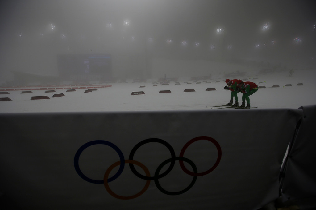 . Two athletes train as the men\'s biathlon 15K mass start was postponed until monday morning because of low visibility, at the 2014 Winter Olympics, Sunday, Feb. 16, 2014, in Krasnaya Polyana, Russia. (AP Photo/Gregorio Borgia)