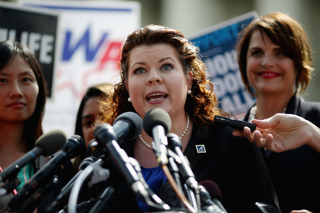 . Lori Windham (C), senior counsel for The Becket Fund for Religious Liberty,addresses the news media in front of the Supreme Court after the decision in Burwell v. Hobby Lobby Stores June 30, 2014 in Washington, DC. (Photo by Chip Somodevilla/Getty Images)