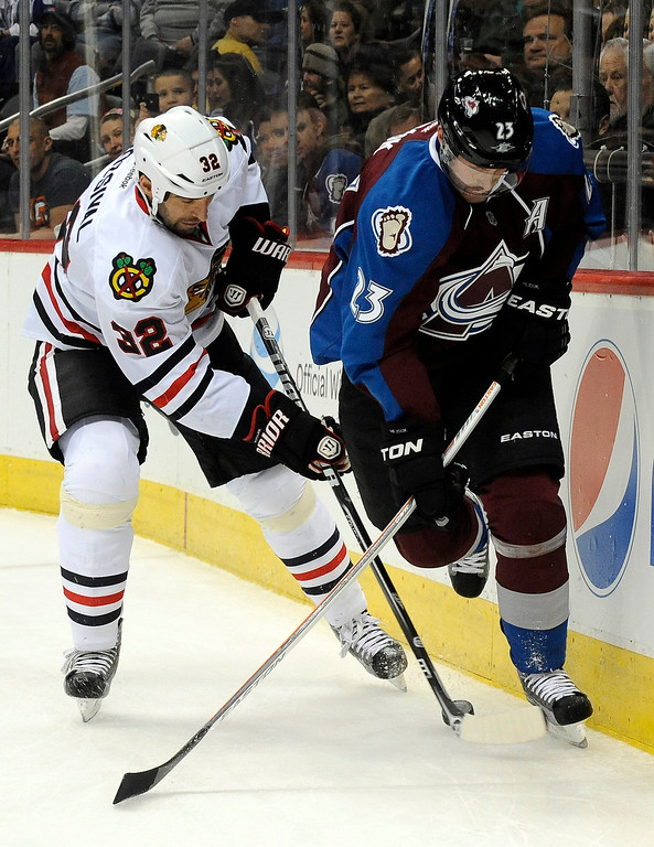 . Chicago Blackhawks defenseman Michal Rozsival (32), of the Czech Republic, and Colorado Avalanche right wing Milan Hejduk (23), also of the Czech Republic, chase the puck into the corner during the first period of an NHL hockey game, Monday, March 18, 2013, in Denver. (AP Photo/Jack Dempsey)