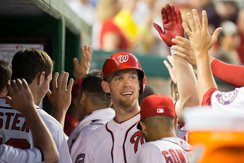 . Washington Nationals Stephen Strasburg is congratulated by teammates after he hit a double, and scored a run on a double hit by teammate Anthony Rendon during the fourth inning of a baseball game against the Colorado Rockies at Nationals Park, on Tuesday, July 1, 2014, in Washington. (AP Photo/Evan Vucci)