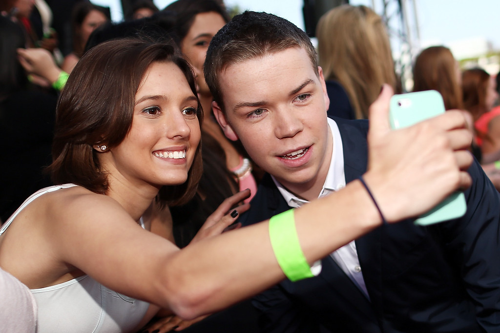 . Actor Will Poulter (R) takes a selfie photo with a fan at the 2014 MTV Movie Awards at Nokia Theatre L.A. Live on April 13, 2014 in Los Angeles, California.  (Photo by Christopher Polk/Getty Images for MTV)