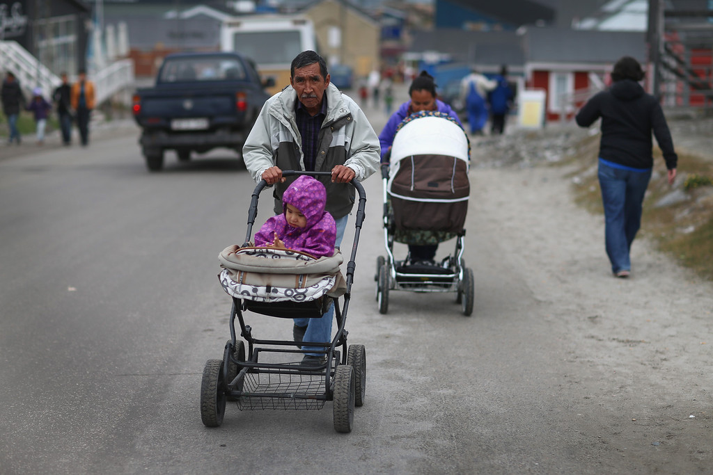 . Pedestrians walk along the road on July 26, 2013 in Ilulissat, Greenland.  (Photo by Joe Raedle/Getty Images)