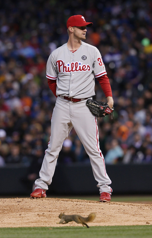 . Philadelphia Phillies starting pitcher Kyle Kendrick waits to throw against the Colorado Rockies as a squirrel, which had been running around the field since the third inning, dashes past the mound in the fourth inning of a baseball game in Denver on Saturday, April 19, 2014. (AP Photo/David Zalubowski)
