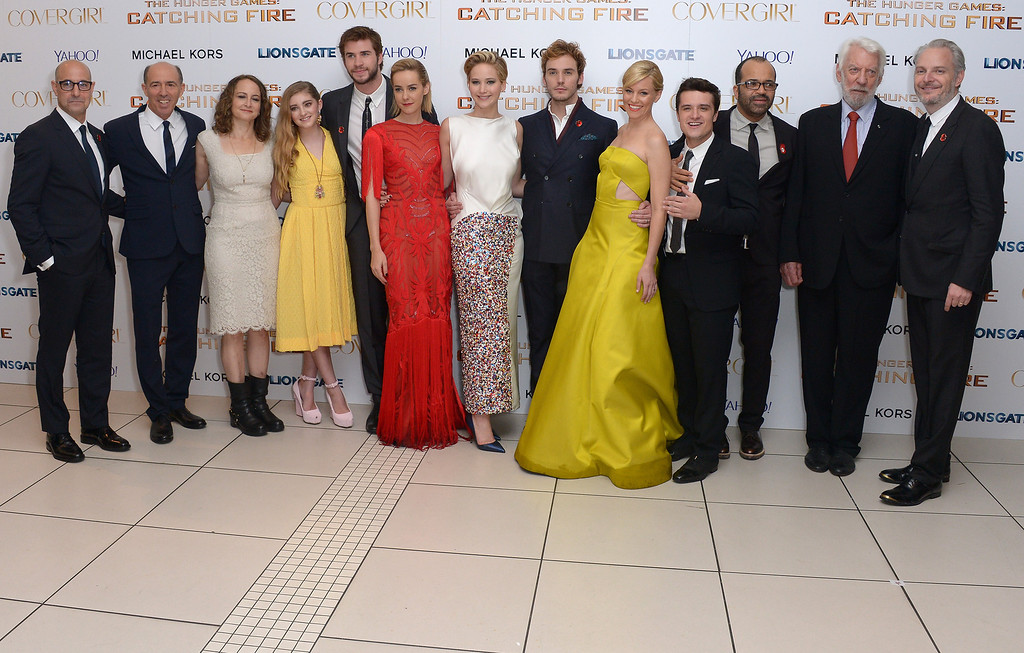 . From left, actor Stanley Tucci, producers Jon Kilik and Nina Jacobson, and other cast members Willow Shield, Liam Hemsworth, Jena Malone, Jennifer Lawrence, Sam Claflin, Elizabeth Banks, Josh Hutcherson, Jeffrey Wright, Donald Sutherland and director Francis Lawrence pose for photographers at the World Premiere of \'The Hunger Games: Catching Fire\', on Monday Nov. 11, 2013, in Leicester Square, London. \'Catching Fire\' is the second installment in \'The Hunger Games\' trilogy. (Photo by Jon Furniss/Invision/AP)