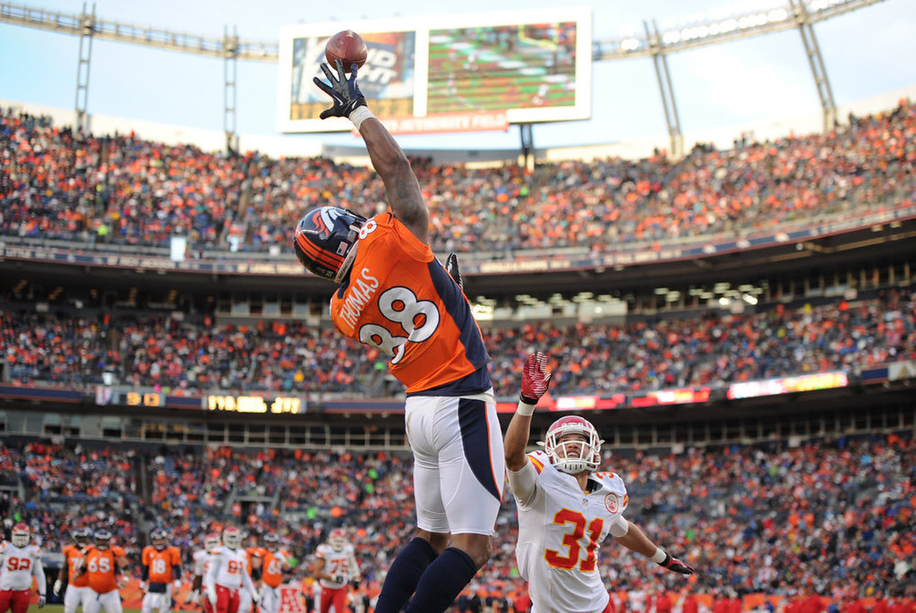 . Denver Broncos wide receiver Demaryius Thomas (88) reaches up for the ball and catches it for a touchdown over Kansas City Chiefs free safety Tysyn Hartman (31) during the third quarter. The Denver Broncos vs Kansas City Chiefs at Sports Authority Field Sunday December 30, 2012. Photo by Joe Amon, The Denver Post