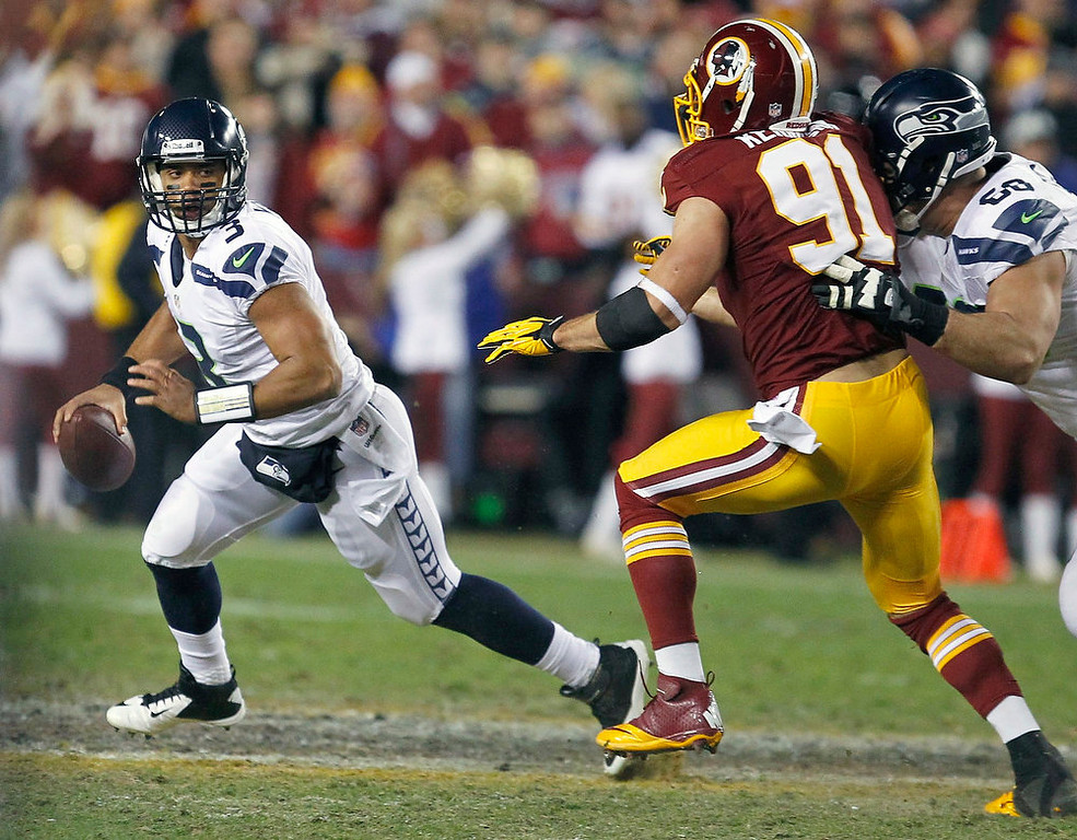 . Seattle Seahawks quarterback Russell Wilson (L) under pressure from Washington Redskins outside linebacker Ryan Kerrigan (91) in the first half during their NFL NFC wildcard playoff football game in Landover, Maryland, January 6, 2013. REUTERS/Tim Shaffer