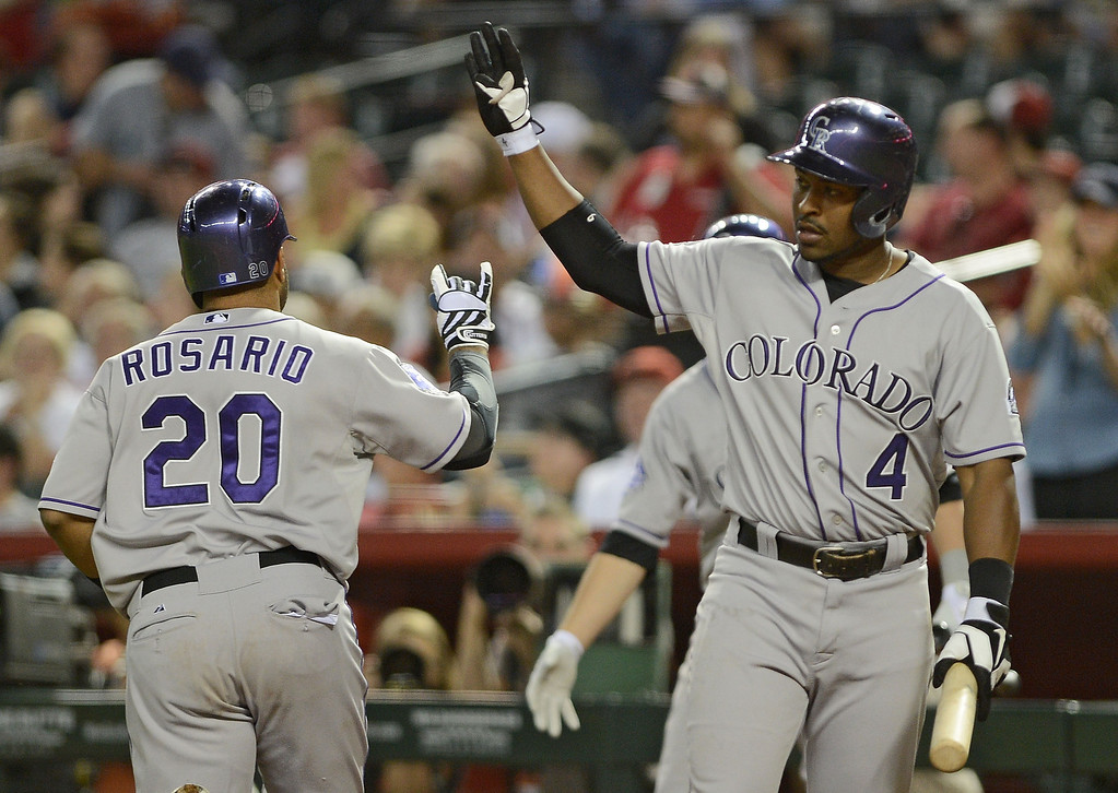 . PHOENIX, AZ - APRIL 26:  Wilin Rosario #20 of the Colorado Rockies is congratulated by teammate Chris Nelson #4 after hitting a solo home run against the Arizona Diamondbacks in the sixth inning at Chase Field on April 26, 2013 in Phoenix, Arizona.  (Photo by Jennifer Stewart/Getty Images)