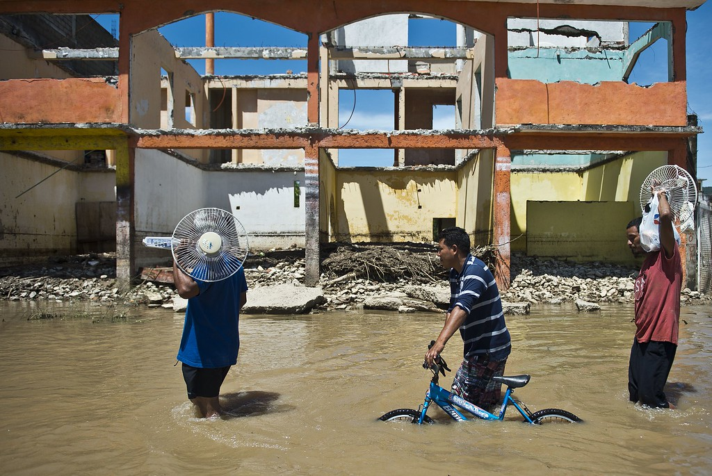 . Local residents wade through a flooded street in Acapulco, state of Guerrero, Mexico, on September 18, 2013 as heavy rains hit the country. Mexican authorities scrambled Tuesday to launch an air lift to evacuate tens of thousands of tourists stranded amid floods in the resort of Acapulco following a pair of deadly storms. The official death toll rose to 47 after the tropical storms, Ingrid and Manuel, swarmed large swaths of the country during a three-day holiday weekend, sparking landslides and causing rivers to overflow in several states. AFP PHOTO/RONALDO  Schemidt/AFP/Getty Images