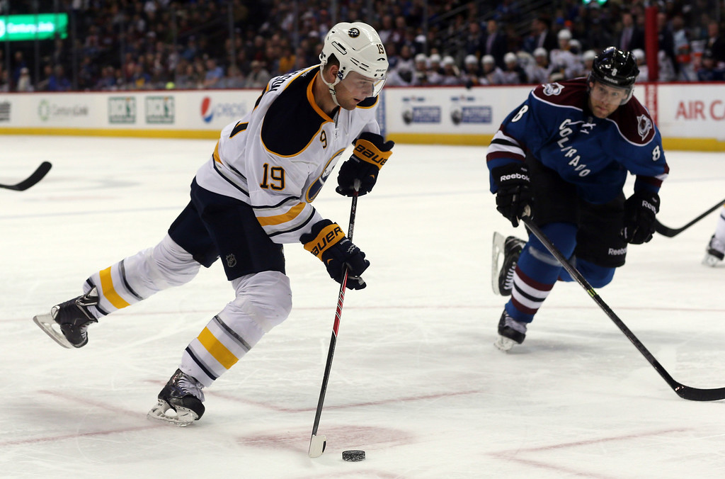 . Buffalo Sabres center Cody Hodgson, front, shoots as Colorado Avalanche defenseman Jan Hejda, of the Czech Republic, covers in the third period of the Avalanche\'s 7-1 victory in an NHL hockey game in Denver, Saturday, Feb. 1, 2014. (AP Photo/David Zalubowski)
