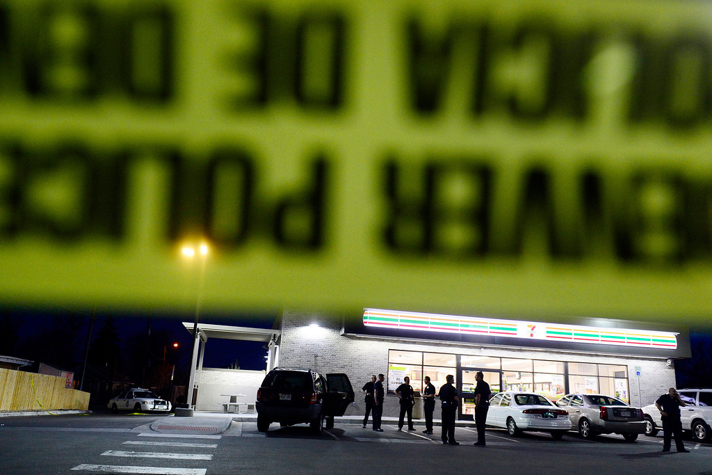 . DENVER, CO - APRIL 29: Officers investigate an SUV at 7-Eleven near 6th and Federal Boulevard after a boy shot nearby and taken to the convenience store. The child who was shot was reported to be in critical condition. (Photo by AAron Ontiveroz/The Denver Post)