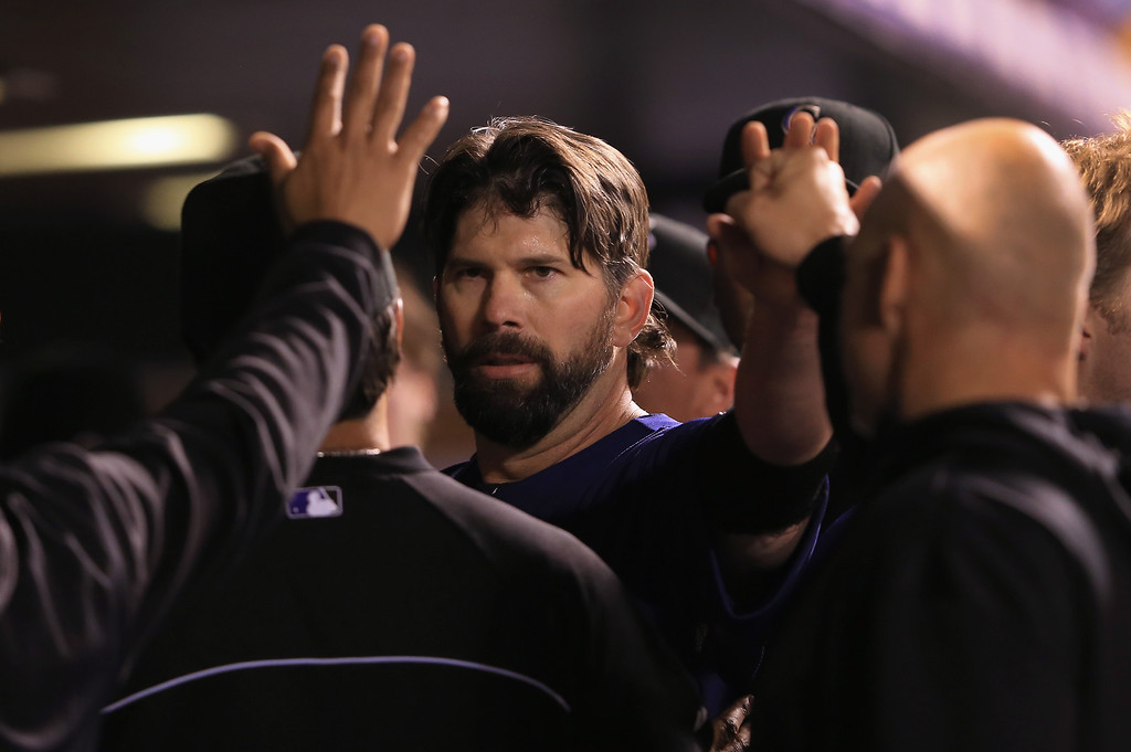 . DENVER, CO - SEPTEMBER 21:  Todd Helton #17 of the Colorado Rockies celebrates in the dugout after scoring on a sacrifice fly by Jordan Pacheco #15 of the Colorado Rockies as the Arizona Diamondbacks held a 6-1 lead in the fourth inning at Coors Field on September 21, 2013 in Denver, Colorado.  (Photo by Doug Pensinger/Getty Images)