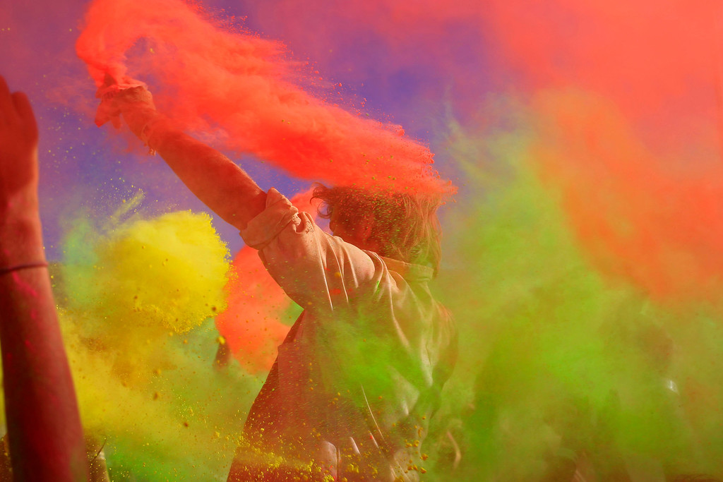 . People throw paint powder in the air during the holi one colour Festival held in the city of Cape Town , South Africa, Saturday, March 2, 2013.  Thousands of people are taking part in the festival by throwing coloured paint powder at each other to express freedom and the colour of everyday life.(AP Photo/Schalk van Zuydam)