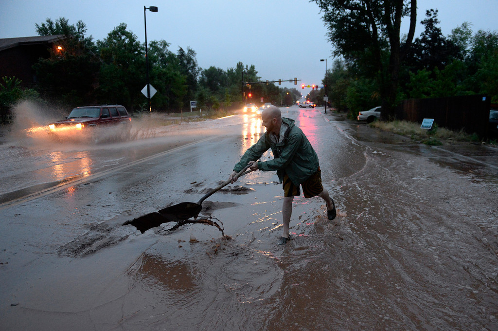 . BOULDER, CO - SEPTEMBER 12: Tommy Stover tries to clear street drains outside his home in north Boulder, September 12, 2013. Massive flash flooding is on going along the Front Range of Colorado. (Photo By RJ Sangosti/The Denver Post)