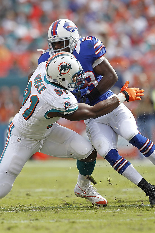 . Cameron Wake #91 of the Miami Dolphins tackles C.J. Spiller #28 of the Buffalo Bills as he runs with the ball on December 23, 2012 at Sun Life Stadium in Miami Gardens, Florida. (Photo by Joel Auerbach/Getty Images)