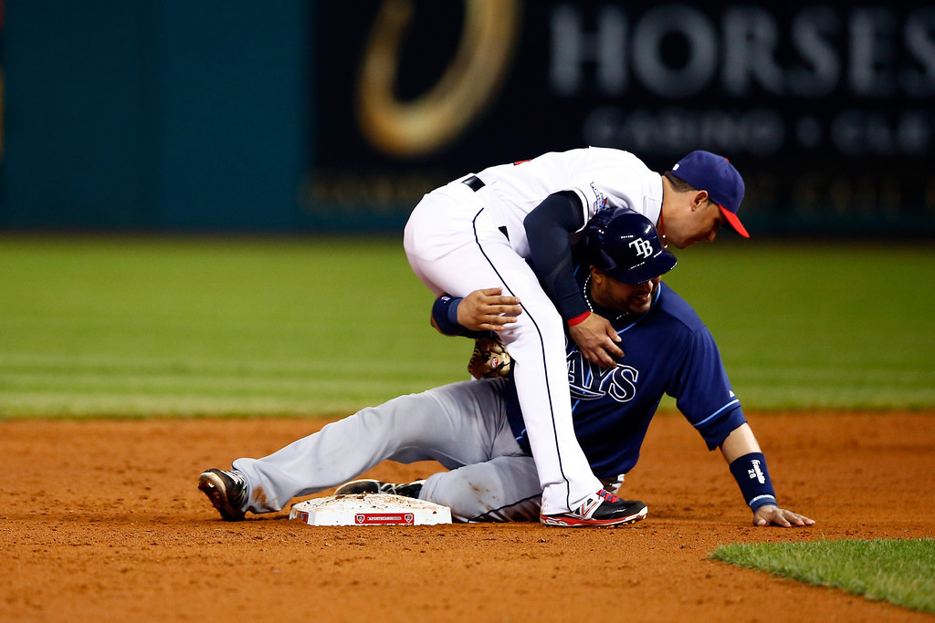 . CLEVELAND, OH - OCTOBER 02:  Jose Molina #28 of the Tampa Bay Rays gets tagged out by Asdrubal Cabrera #13 of the Cleveland Indians to end the top outfield the fifth inning during the American League Wild Card game at Progressive Field on October 2, 2013 in Cleveland, Ohio.  (Photo by Jared Wickerham/Getty Images)
