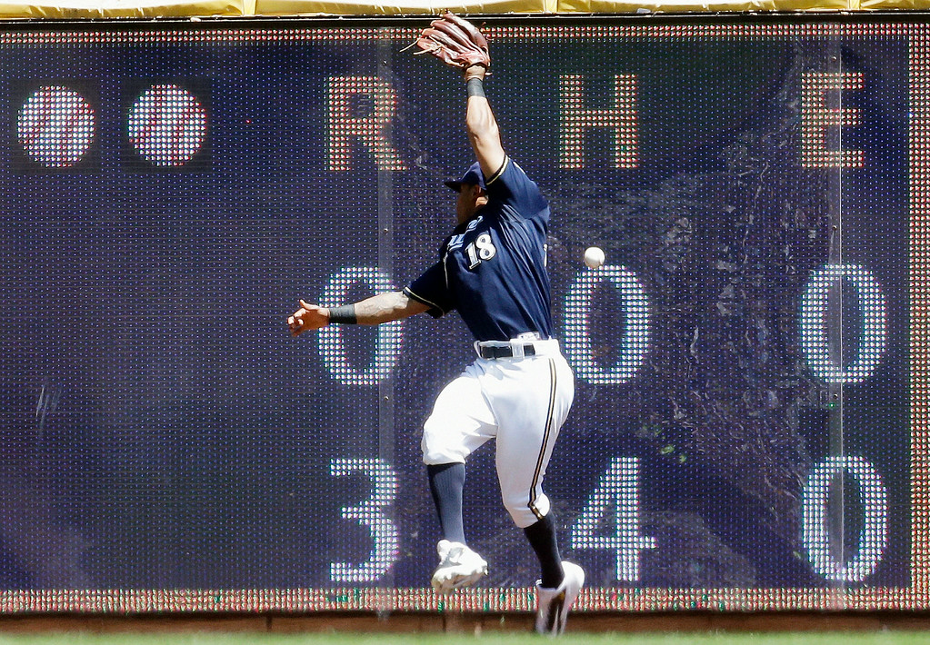 . Milwaukee Brewers left fielder Khris Davis can\'t catch a ball hit by Colorado Rockies\' Brandon Barnes during the second inning of a baseball game Sunday, June 29, 2014, in Milwaukee. (AP Photo/Morry Gash)