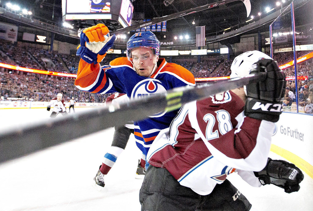 . Colorado Avalanche\'s Paul Carey (28) is checked by Edmonton Oilers\' Anton Lander (51) during first period NHL hockey action in Edmonton, Alberta, on Tuesday April 8, 2014. (AP Photo/The Canadian Press, Jason Franson)