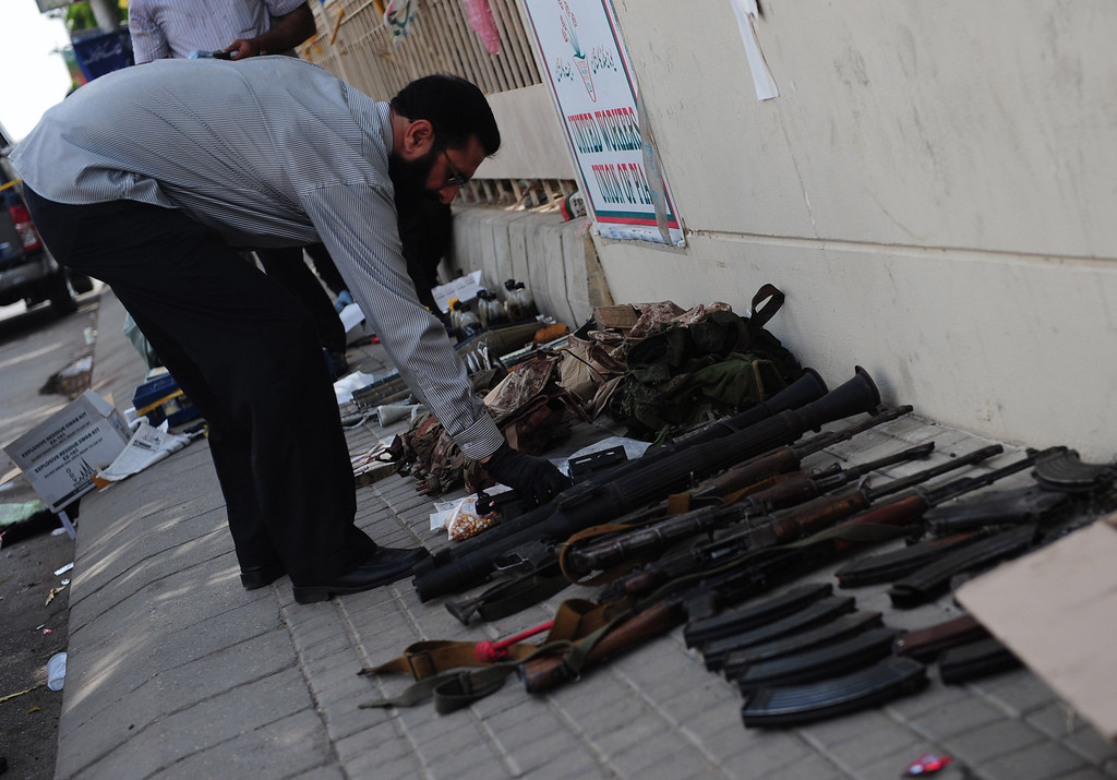 . A Pakistani investigator inspects weapons seized from militants following an assault by militants at Karachi airport in Karachi on June 9, 2014. AFP PHOTO/Rizwan  TABASSUM/AFP/Getty Images