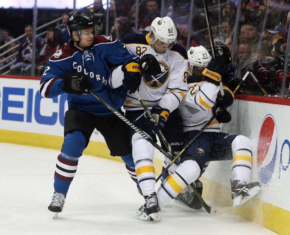 . Colorado Avalanche defenseman Nick Holden, left, battles for control of the puck with Buffalo Sabres left wing Marcus Foligno, center, and right wing Matt D\'Agostini in the first period of an NHL hockey game in Denver, Saturday, Feb. 1, 2014. (AP Photo/David Zalubowski)