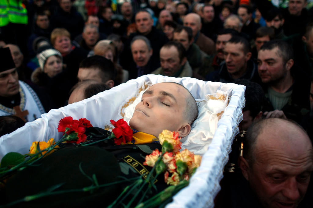 . The body of an anti-government protester killed in clashes with the police is carried by protesters at Independence Square in Kiev, Ukraine, Friday, Feb. 21, 2014. (AP Photo/ Marko Drobnjakovic)