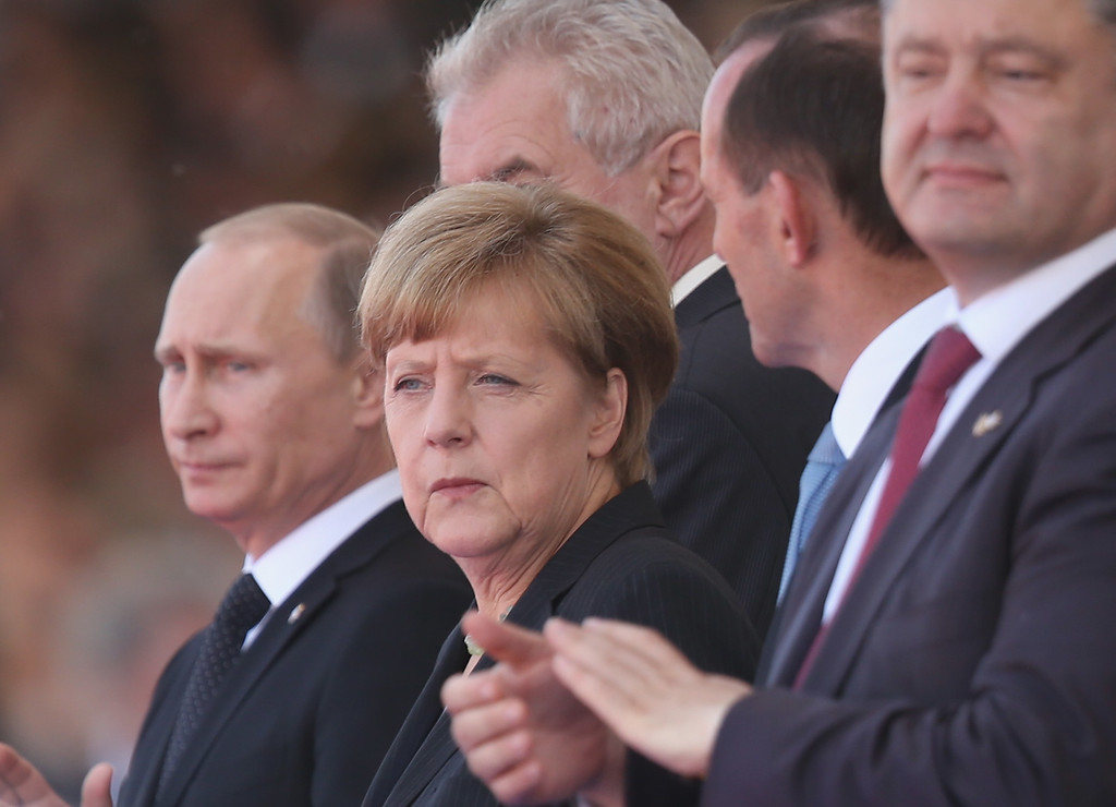 . Russian President Vladimir Putin (L), German Chancellor Angela Merkel and Ukrainian President Petro Poroshenko (R) attend the main international ceremony with 17 heads of state at Sword Beach on June 6, 2014 at Ouistreham, France.  (Photo by Sean Gallup/Getty Images)