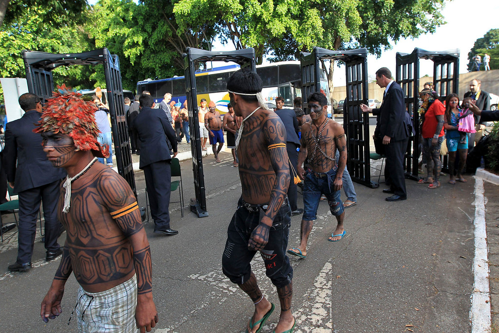 . Munduruku Indians pass through a metal detector as they arrive for a meeting with the Minister of the General Secretariat of the Presidency of Brazil, Gilberto Carvalho, at the Planalto Palace in Brasilia, June 4, 2013. President Dilma Rousseff\'s government sought on Tuesday to defuse mounting conflicts with indigenous groups over its decision to stop setting aside farm land for Indians and plans to build more hydroelectric dams in the Amazon. The government flew 144 Munduruku Indians to Brasilia for talks to end a week-long occupation of the controversial Belo Monte dam on the Xingu river, a huge project aimed at feeding Brazil\'s fast-growing demand for electricity. REUTERS/Ueslei Marcelino