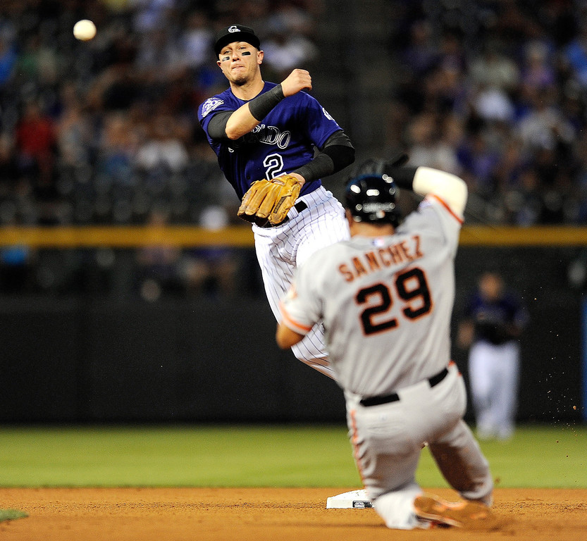 . Colorado Rockies\' Troy Tulowitzki (2) forces out San Francisco Giants\' Hector Sanchez (29)  at second as he turns a double player hit into by Roger Kieschnick  during the fourth inning of a baseball game on Tuesday, Aug. 27, 2013, in Denver. (AP Photo/Jack Dempsey)