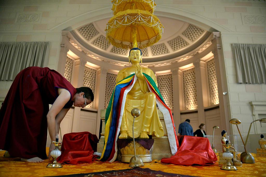 . Venerable Norbu, a Buddhist nun, prepares the alter around the Maitreya Buddha at the Zen Center of Denver in Denver, CO August 23, 2013. (Photo By Craig F. Walker / The Denver Post)