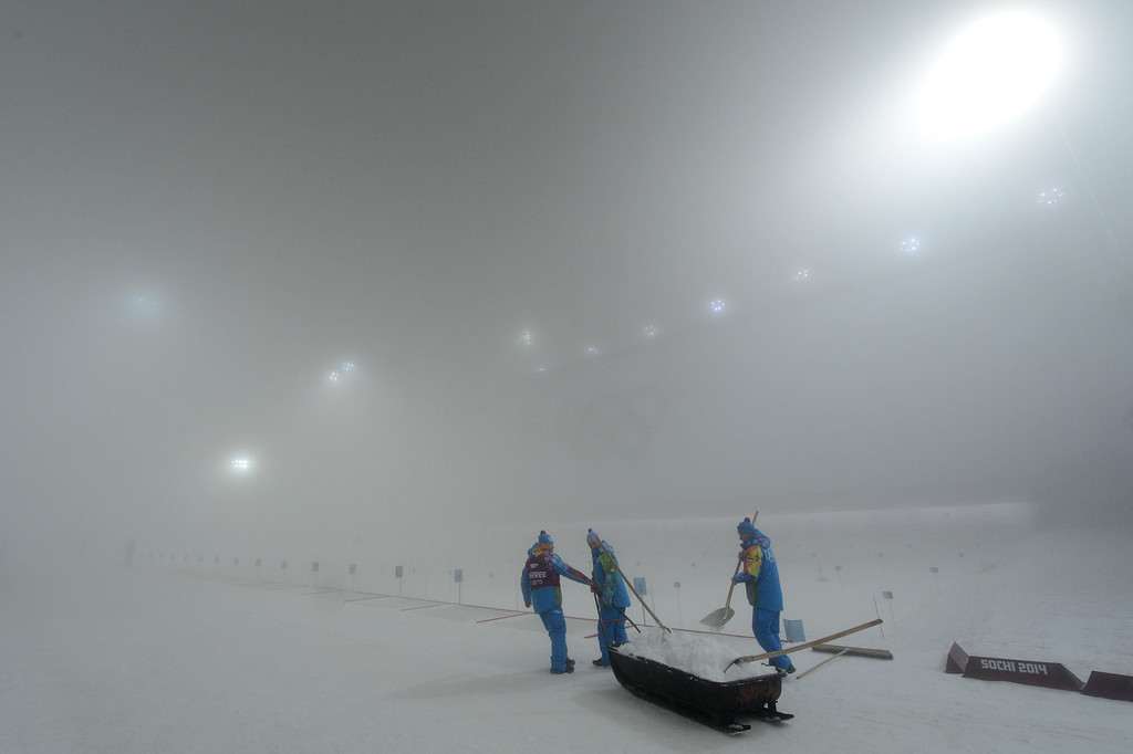 . Volunteers transport snow to prepare the shooting range as the Men\'s Biathlon 15 km Mass Start has been postponed until the next day due to fog at the Laura Cross-Country Ski and Biathlon Center during the Sochi Winter Olympics on February 16, 2014, in Rosa Khutor, near Sochi.  KIRILL KUDRYAVTSEV/AFP/Getty Images