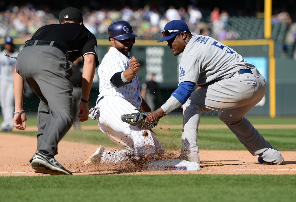 . DENVER, CO - JULY 5:  Los Angeles third baseman Juan Uribe put the tag on Wilin Rosario after he tried to advance to third on a caught fly ball in the eighth inning. The Colorado Rockies defeated the Los Angeles Dodgers 8-7 at Coors Field Saturday afternoon, July 5, 2014.  Photo by Karl Gehring/The Denver Post