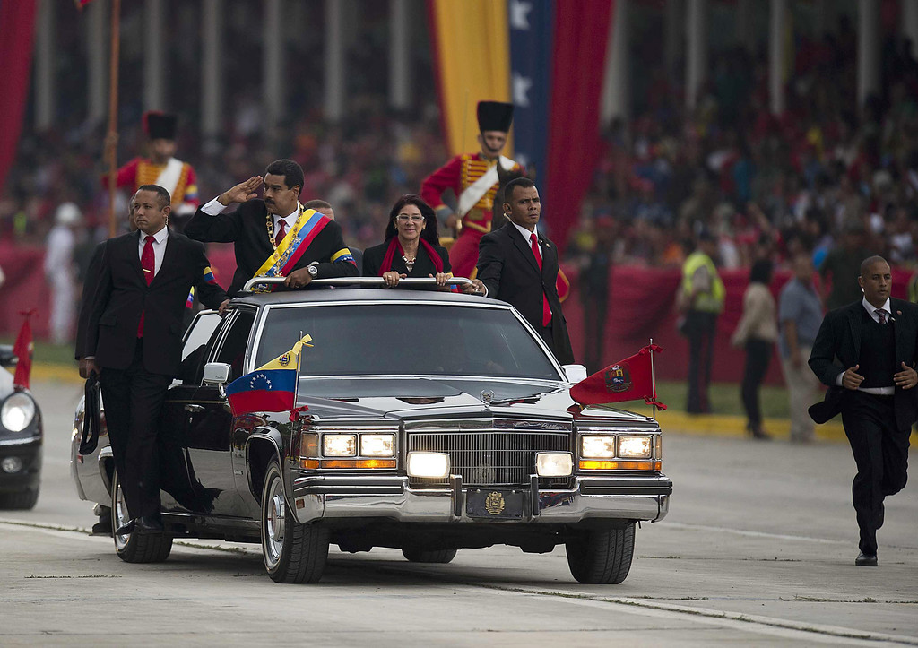 . Venezuelan President Nicolas Maduro (C) salutes militay-style during a motorcade after his installation in Caracas on April 19, 2013.  LUIS ACOSTA/AFP/Getty Images
