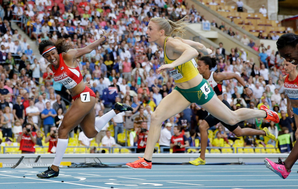 . United States\' Brianna Rollins, left, gold, andAustralia\'s Sally Pearson, silver, cross the finish line in the women\'s 100-meter hurdles final at the World Athletics Championships in the Luzhniki stadium in Moscow, Russia, Saturday, Aug. 17, 2013. (AP Photo/David J. Phillip)
