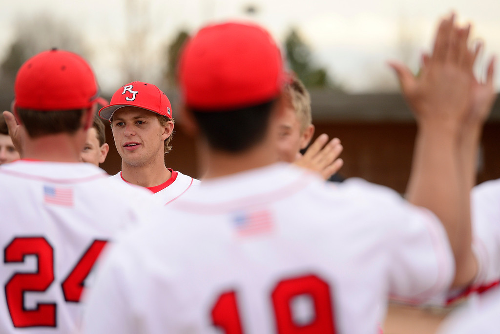 . PARKER, CO - APRIL 29: Regis Jesuit shortstop Brody Weiss and teammates high five following a 10-0 win in the team\'s final home game. Weiss is the son of Colorado Rockies manager Walt Weiss. (Photo by AAron Ontiveroz/The Denver Post)