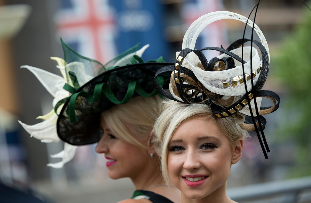 . Sharon Teague, left and her daughter Ellie wear ornate hats as they pose for photographers on the third day of the Royal Ascot horse racing meeting, which is traditionally known as Ladies Day, at Ascot, England,  Thursday, June, 19, 2014.  Royal Ascot the annual five day horse race meeting that Britain\'s Queen Elizabeth II attends every day of the event. (AP Photo/Alastair Grant)