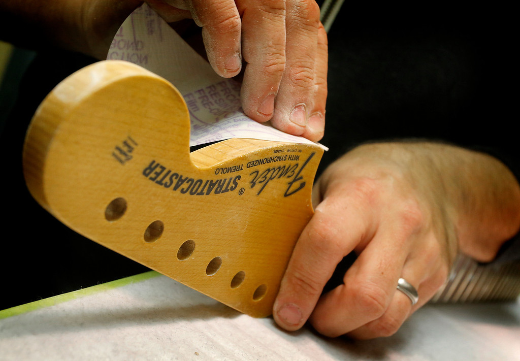. A Fender Stratocaster head stock is sanded in the Fender Custom Shop at the factory in Corona, Calif. on Tuesday, Oct. 15, 2013. Leo Fender developed the instrument in a small workshop in Fullerton, Calif. six decades ago. (AP Photo/Matt York)