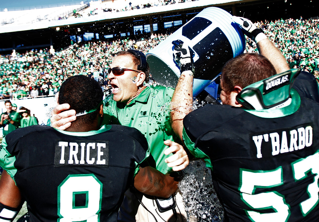 . North Texas defensive back Marcus Trice (8) and offensive lineman Mason Y\'Barbo (57) douse head coach Dan McCarney following their 36-14 win over UNLV in the Heart of Dallas NCAA college football game, Wednesday, Jan. 1, 2014, in Dallas. (AP Photo/Mike Stone)