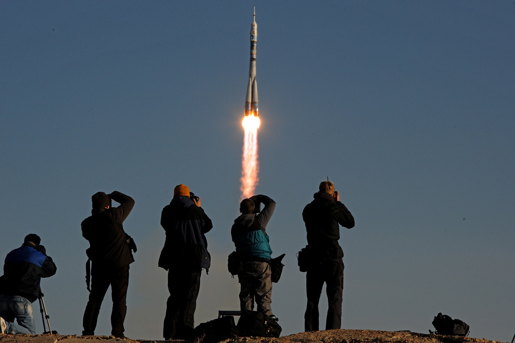. People take photographs as Russia\'s Soyuz TMA-11M spacecraft carrying an international crew including Japanese astronaut Koichi Wakata, Russian cosmonaut Mikhail Tyurin and US astronaut Rick Mastracchio and an unlit Olympic torch for the 2014 Winter Games in Sochi aboard blasts off from the Russian leased Kazakh Baikonur cosmodrome on November 7, 2013. Two Russian astronauts will take the unlit torch on a space walk on November 9 before it returns back to Earth on November 11. AFP PHOTO/KIRILL  KUDRYAVTSEV/AFP/Getty Images