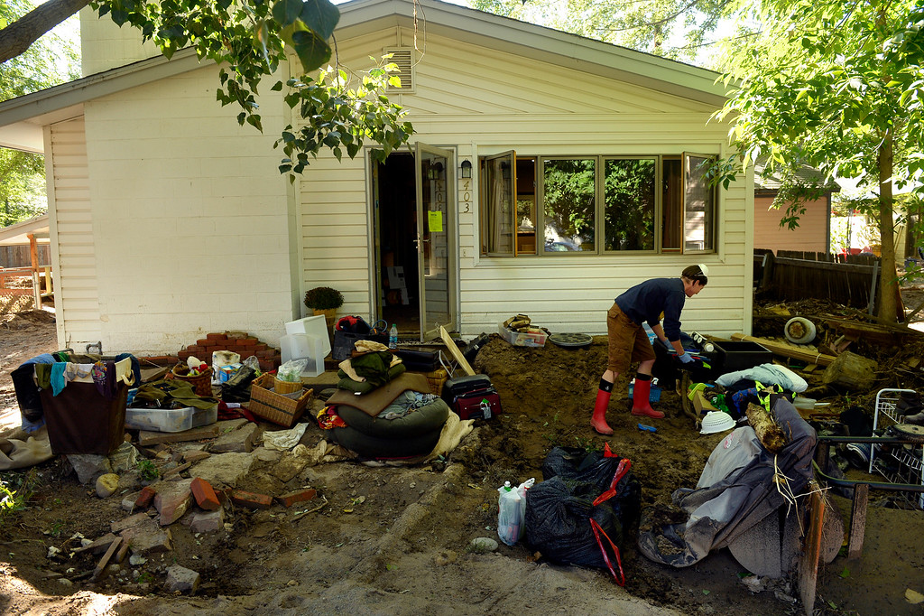 ". Brenna Willis works outside the home she shares with her partner Emma Birath in Lyons, CO September 20, 2013. She said they had 10 inches of water in the house and they were trying to salvage what they could.  Birath said, ""when we got here it was a bit of a shock. It looked worse than we thought. Water can do a lot of damage.\"" Friday was the second day residents were allowed to return to their homes.  (Photo By Craig F. Walker / The Denver Post)"