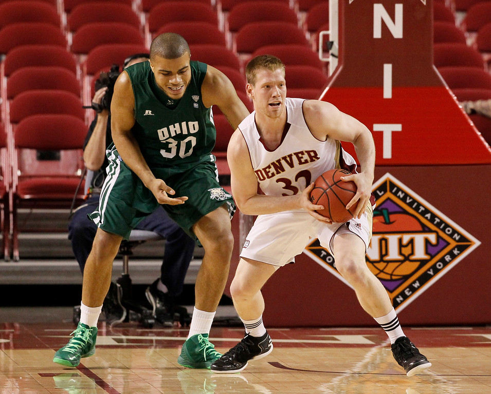 . Denver guard Chase Hallam, right, picks up a loose ball in front of Ohio forward Reggie Keely in the second half of Denver\'s 61-57 victory in a first-round NIT college basketball game in Denver on Tuesday, March 19, 2013. (AP Photo/David Zalubowski)