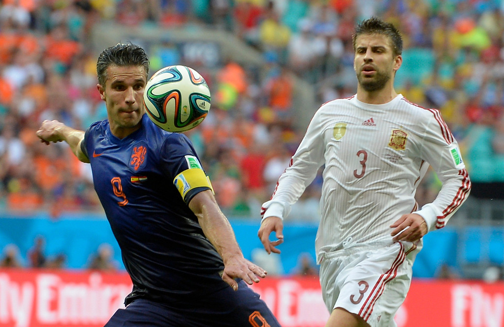 . Netherlands\' Robin van Persie, left, prepares to take a shot watched by Spain\'s Gerard Pique during the group B World Cup soccer match between Spain and the Netherlands at the Arena Ponte Nova in Salvador, Brazil, Friday, June 13, 2014. (AP Photo/Manu Fernandez)