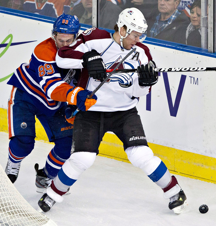 . Colorado Avalanche\'s Paul Stastny elbows Edmonton Oilers\' Sam Gagner as they battle for the puck during the first period of an NHL hockey game in Edmonton, Alberta, on Saturday Feb. 16, 2013. (AP Photo/The Canadian Press, Jason Franson)