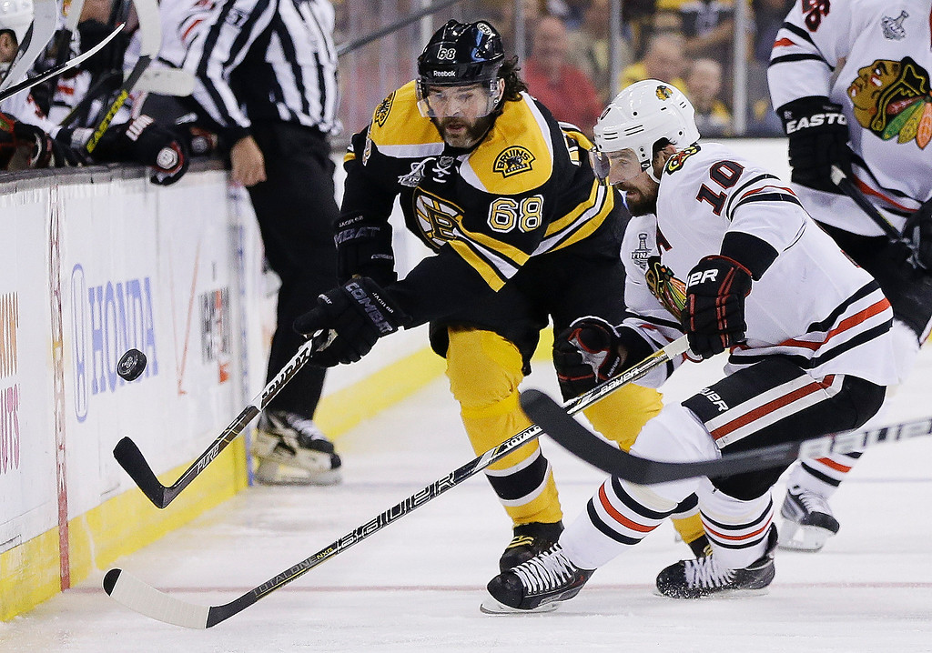 . Chicago Blackhawks center Patrick Sharp (10) and Boston Bruins right wing Jaromir Jagr (68), of the Czech Republic, pursue the puck during the first period in Game 6 of the NHL hockey Stanley Cup Finals Monday, June 24, 2013 in Boston. (AP Photo/Elise Amendola)
